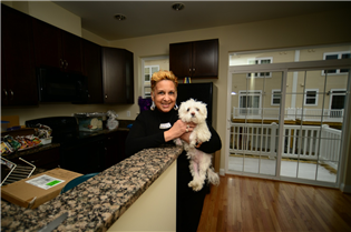 Charlese Jennings and her dog, Deogie, take a break from moving into their new home at MetroTowns.
