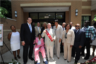 New residents, community members, and officials pose in front of DCHA's new assisted living facility.