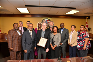 Robert Pohlman (third from left) is honored by DCHA Executive Director Adrianne Todman (fourth from left), Board Chairman Pedro Alfonson (second from left) and the Board of Commissioners.