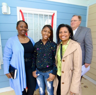 Diweena Streater stands on her porch after the ribbon-cutting for her new Habitat for Humanity home.  Next to her are daughter Nia Streater,  Adrianne Todman, Executive Director for the DC Housing Authority and Bruce Reed from Marriott International, the corporate sponsor of this home.