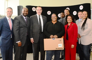 Lucky Montana Terrace resident Deraine Tittman (holding box) won the laptop at the DCHA-One Economy news conference held at her computer training class.  Left to right:  David Saunier, President, One Economy; Ken Jones, Rent A Center, Mayor Gray; Ms. Tittman; Adrianne Todman, DCHA Executive Director; Tanora Gibbs, Resident council President.  Row 2:  Nathan Bovelle, DCHA; Kenyan McDuffie, Ward 5 Councilmember;  Rob Mancini, DC Chief Technology Officer.